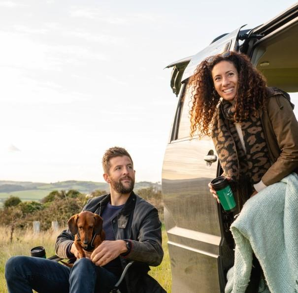 Couple with dog sitting outside of camper