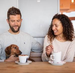 Couple drinking hot drinks with dog on lap