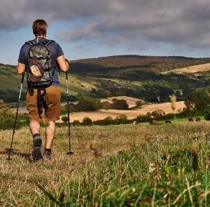 Man walking through countryside with views of rolling hills