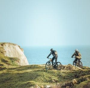 Two people cycling along cliff