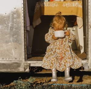 Girl sitting on step of airstream caravan drinking from a cup