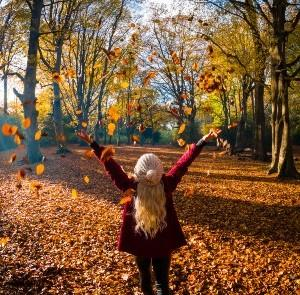 Lady throwing Autumn leaves in the air