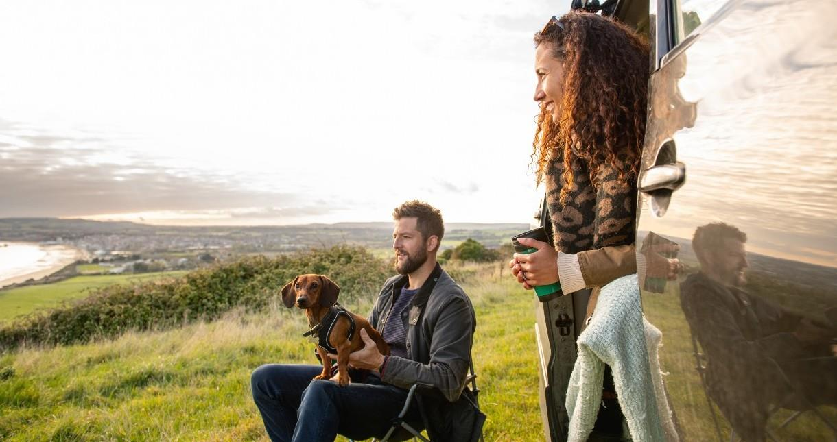 Couple with dog in camper van looking out to sea, Isle of Wight