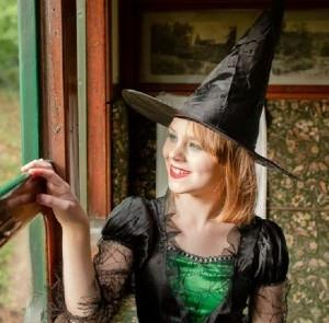 Lady dressed up as a witch sitting on the train at the Isle of Wight Steam Railway