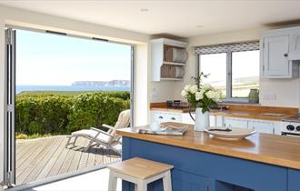 Kitchen area with folding doors onto patio at Flackstead, Isle of Wight, Self Catering
