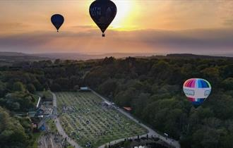 Credit - IOWightDrone - Aerial view of hot air balloons floating above Robin Hill, Sky High Nigh Glow, What's On, Isle of Wight