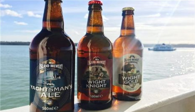 Three bottles of beer on ledge overlooking solent with ferry in background, Isle of Wight, Local Produce, Island Brewery, let's buy local