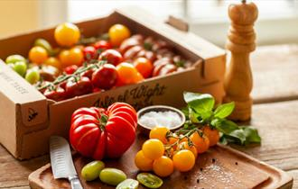Tomatoes produced by The Tomato Stall on a chopping board and various types of tomatoes in a box, local produce, Isle of Wight, let's buy local