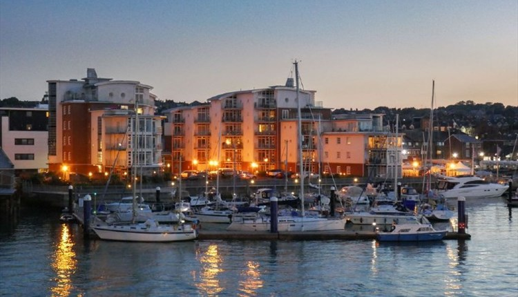 Isle of Wight, Quay Management, Self Catering Agency, Accommodation, image of apartment block over looking marina at night