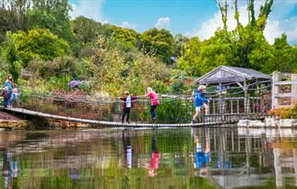 Family on bridge across lake at Robin Hill - Things to Do, Isle of Wight.