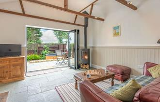 The Stables living room with french doors opening to the garden with hot tub - Kingates Farm Cottages, Isle of Wight, Self Catering