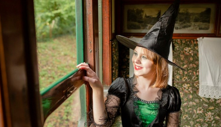 Isle of Wight, Things to Do, Isle of Wight Steam Railway, Wizard Week, Image of lady in witch costume looking out of carriage window.