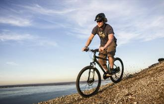 Man on mountain bike along cliff, Tackt-Isle Adventures, Isle of Wight, Things to Do