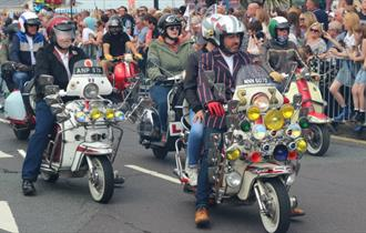 Isle of Wight Scooter Rally, image of Scooter Riders riding along road with onlookers applauding