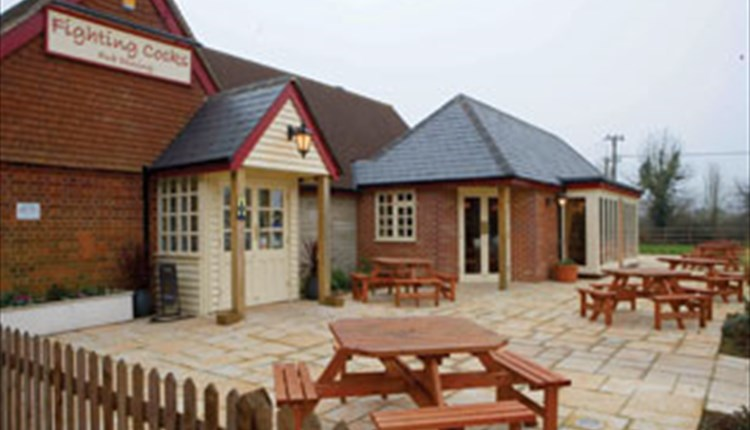 Outside view of The Fighting Cocks with outside eating area, Arreton, pub