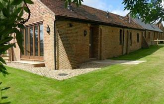 Outside view of Lacewood barn surrounded by garden, Fernhill Barns, Wootton, Isle of Wight, self-catering