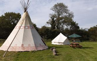 Outside view of tipi with a bell tent and picnic bench next door, Isle of Wight Tipi Holidays, glamping
