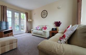 Lounge with french doors opening onto the patio in the garden at West View Holiday Cottage, Ryde, Self-catering
