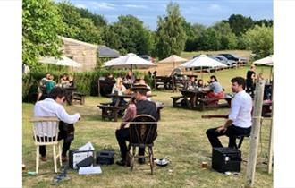 Isle of Wight, Things to Do, Garlic Farm, Eating Out, Event, Pizza and Jazz evening, image of musicians playing in garden with tables and parasols loo