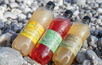 Selection of soft drinks produced by Wight Crystal laid on the beach, Isle of Wight, local produce, let's buy local