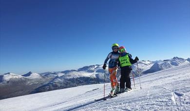 Bilde fra bakken med to skiløpere. strålende sol, blå himmel. Galdhøpiggen sommerskisenter, Galdhøpiggen summer skiing center, juvass