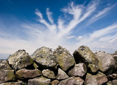 Dry stone wall with blue sky and clouds.