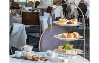 Afternoon tea serving on a tiered display of scones, sandwiches and assorted cakes.