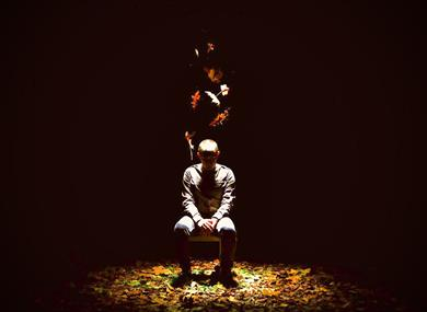 Image credit Drew Forsyth.  A man sit on a chair on the stage surrounded in darkness with the spotlight on him.  Autumn leaves fall from above and are