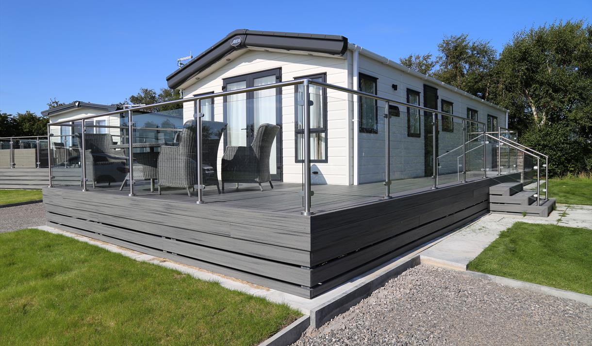 Caravan with grey decking and glass fence