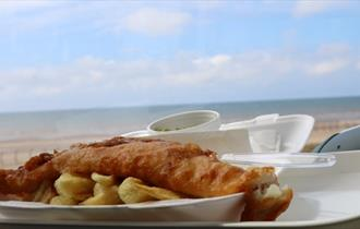 A plate of fish and chips against the backdrop of Blackpool beach on a sunny day.