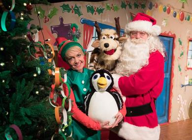Santa poses in his workshop with an elf, a penguin and a reindeer.