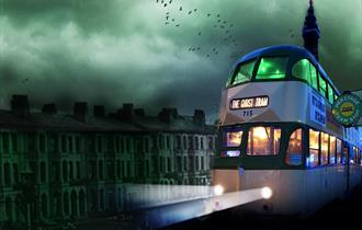 A heritage tram travels through Blackpool, past the Blackpool Tower.  Headlights are on and spooky bats fly in the eyry sky.