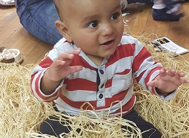 A happy toddler is sat amongst straw like material, reaching out to touch it.