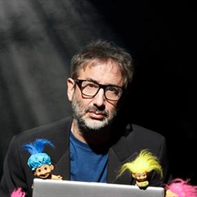 A man holding a laptop and some troll dolls
