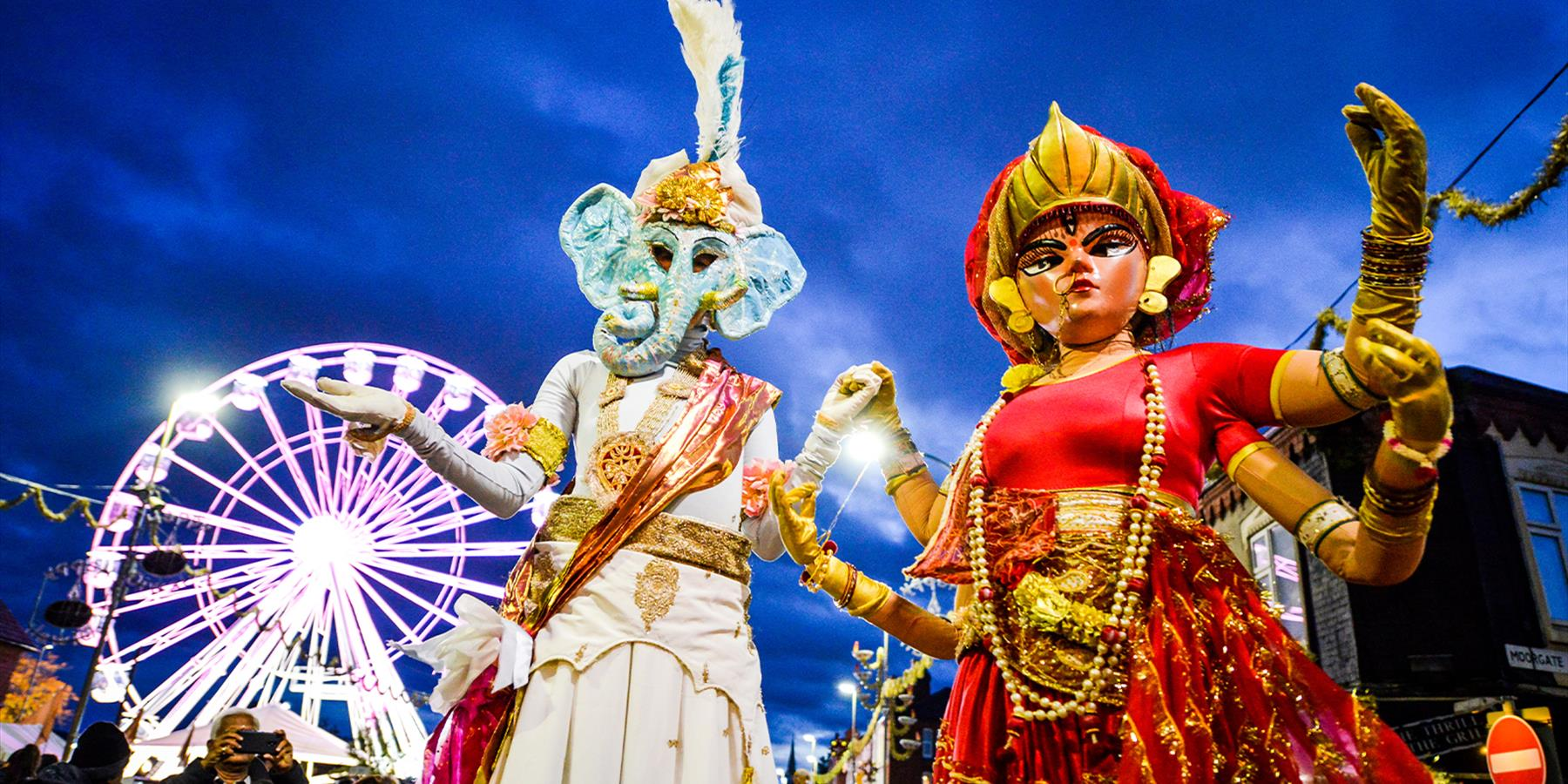 golden mile figures with wheel in background on diwali