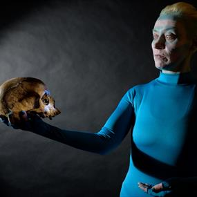 Emily Carding is pictured holding a skull in her hand which is held in the air. She is wearing a blue morph suit and has blue face paint on. Her hair