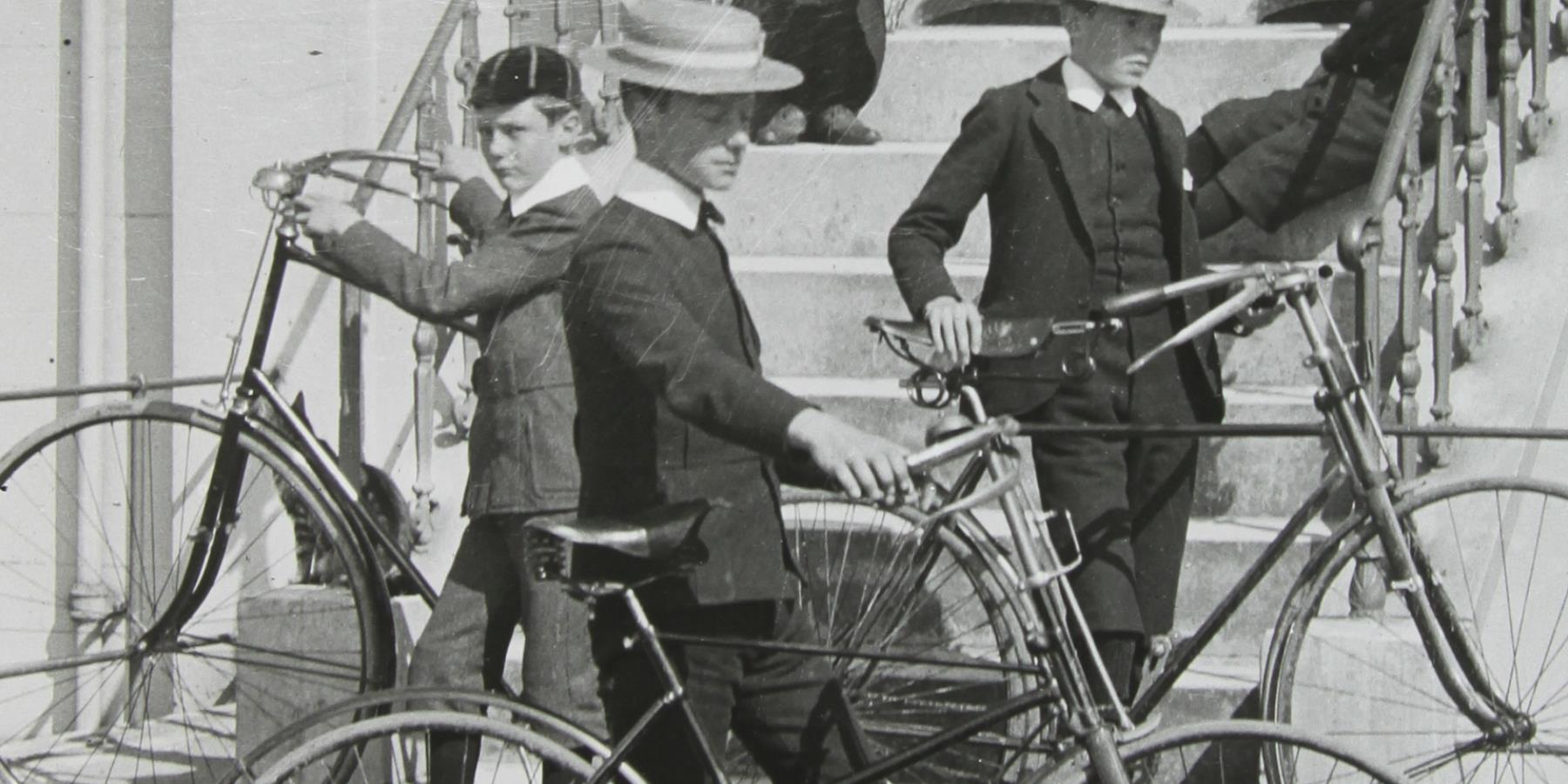 Group of people sitting and standing on steps with bicycles
