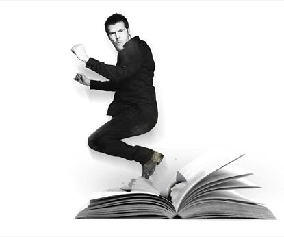 A man crouching on a book