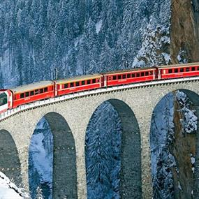 A train crossing a bridge in the mountains