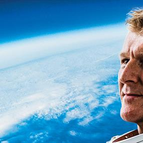A man in a space suit looking at the Earth
