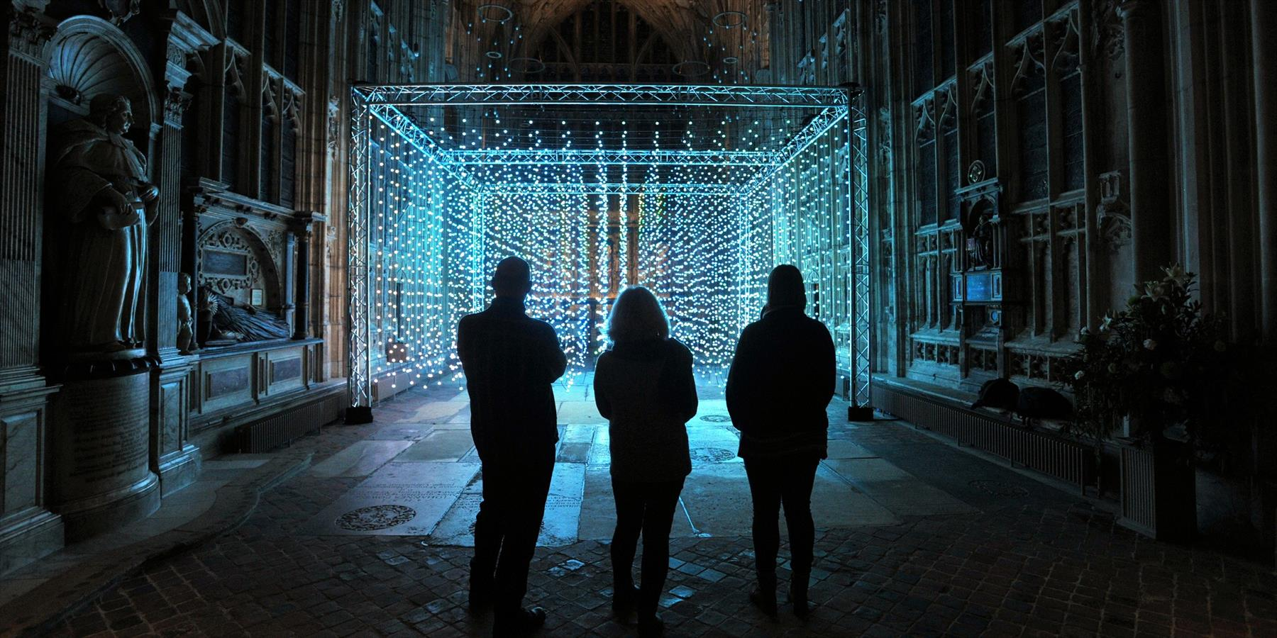 People standing in a cathedral in front of a light installation