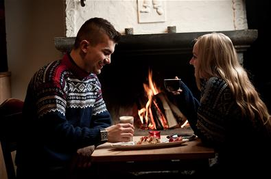 A couple who enjoy a cup of coffee in front of the fireplace.