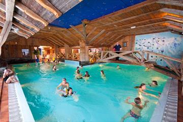 Svømmebasseng med klatrevegg. Folk som svømmer og leker seg i vannet. Spidsbergseter Resort Rondane.