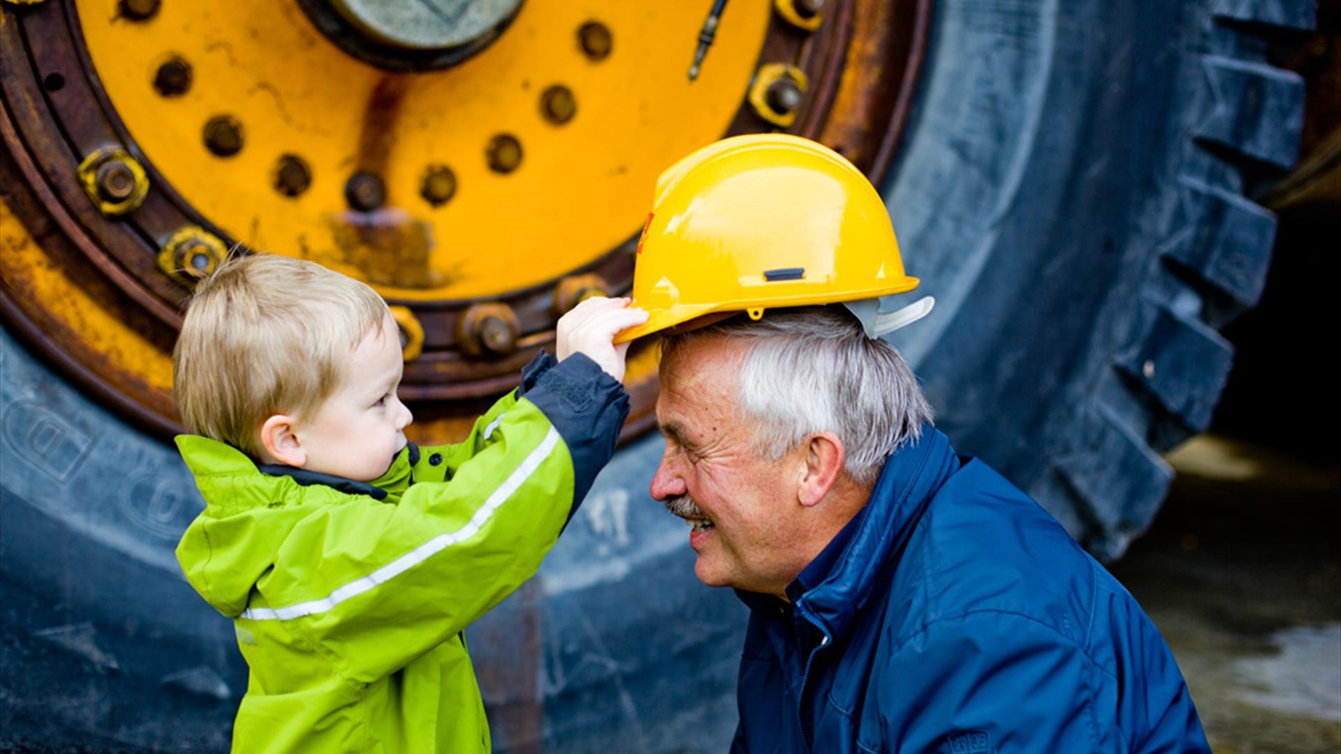 Gutt setter hjelmen på Bestefar hos Norsk Fjellsprengingsmuseum