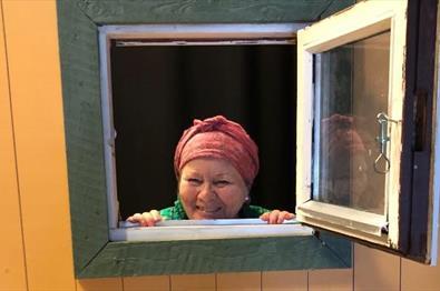 Dame titter ut av vinduet
