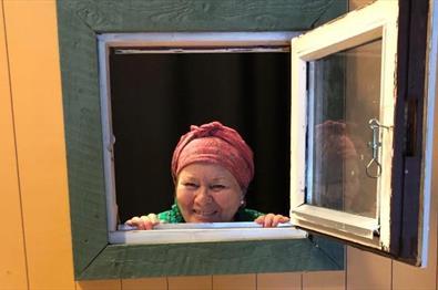 Dame titter ut av vindu