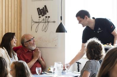 The host, Geir, serve guests at Stasjonen Cafe & Restaurant