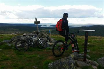 Mountain biker at the top of the mountian Snørvillen at Sjusjøen with a view towards mountains mountains in the distance.