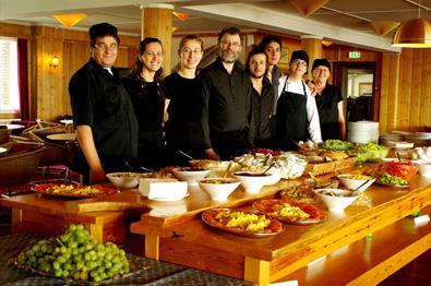 Kokker og servitører på Hornsjø Høyfjellshotell har stilt seg opp foran den deilige buffeten.