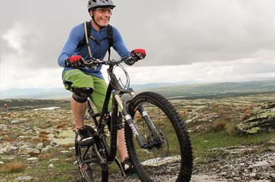 Mann auf einem Mountainbike, der aktiv einen Phad in der Skeikampen-Gegend radelt.